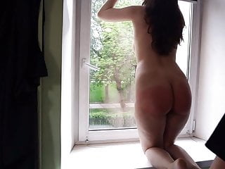 Young lady is spanked with a belt in front of the window