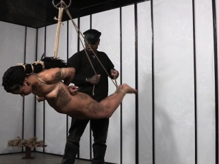 Tattooed black sub suspended by maledom